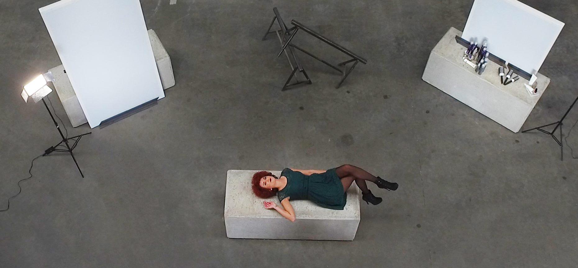 Frau liegt auf weißem Stein